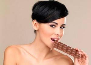 Девушка кушает шоколадку