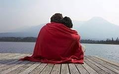 Мужчина на берегу обнимает женщину