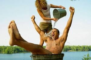 Девушка поливает водой парня