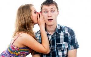 Девушка говорит парню на ухо